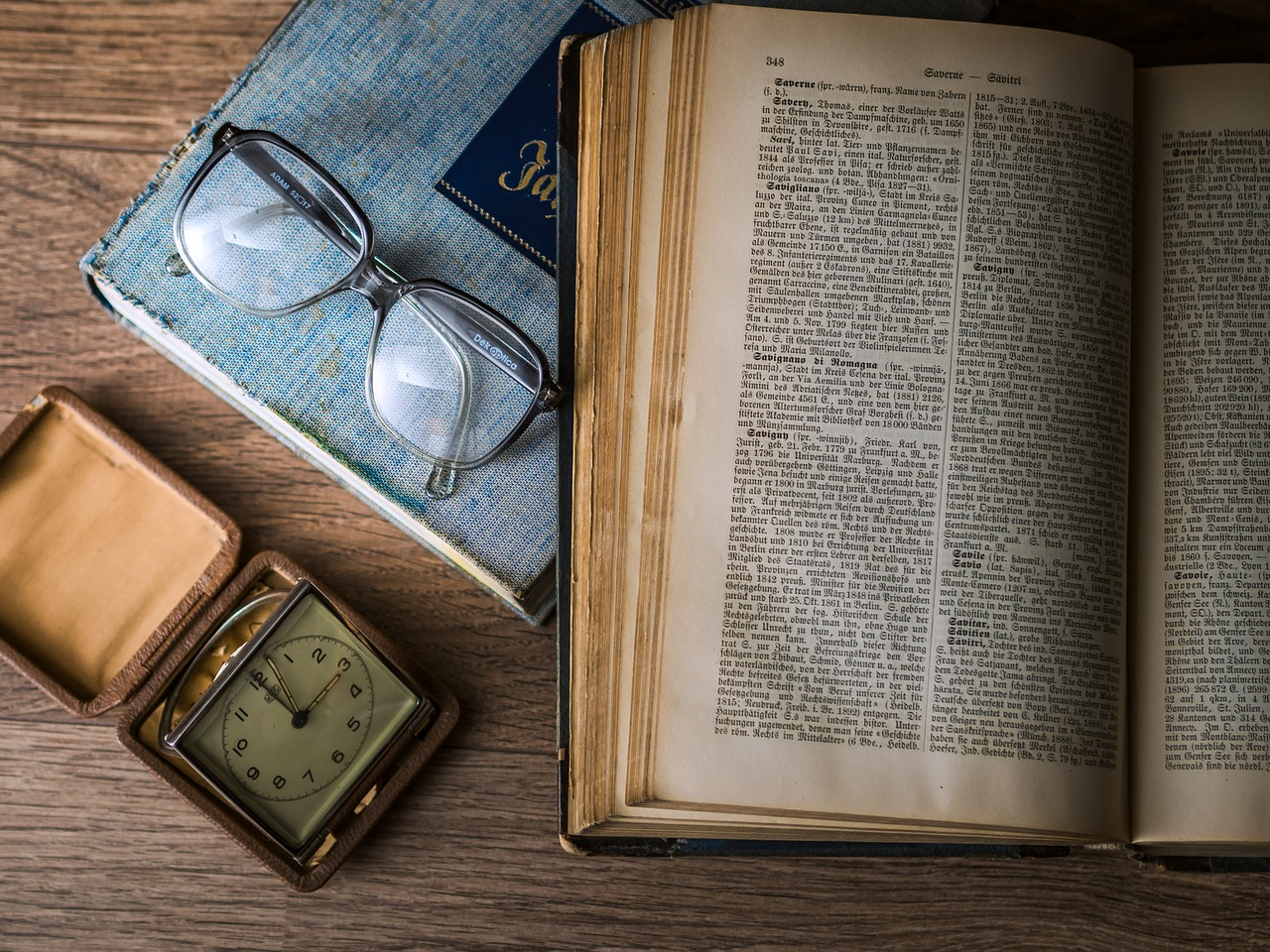 historical book, glasses, clock